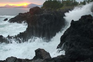 1280px-Jungmun_Daepo_Columnar_Joints_with_waves_crashing